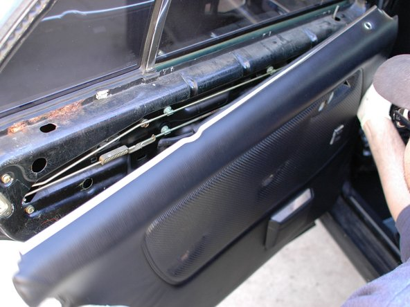 Remove the panel by pulling up on it. Do not pull straight out on the panel, or it may bend. This cannot be repaired. Pulling up on the panel before pulling out on it will also help ensure that you do not damage the plastic clips on the back of the map pocket on the door panel (only applies to front panels; rear panel shown in this picture).