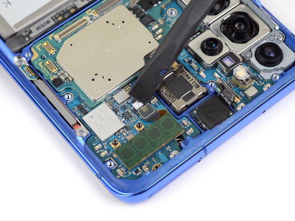 Pry up and disconnect the upper 5G antenna cable from the motherboard.