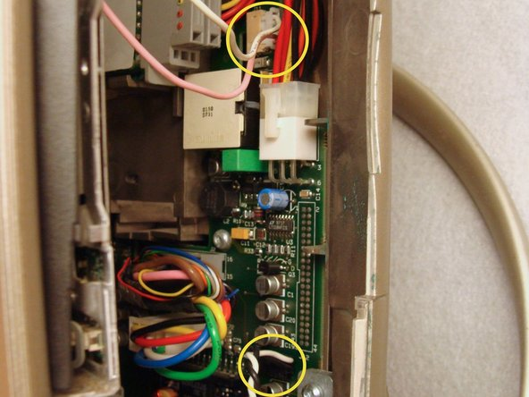 Disconnect the pink and white backlight inverter cable and the black and white right speaker cable from behind the floppy disk drive on the right side.