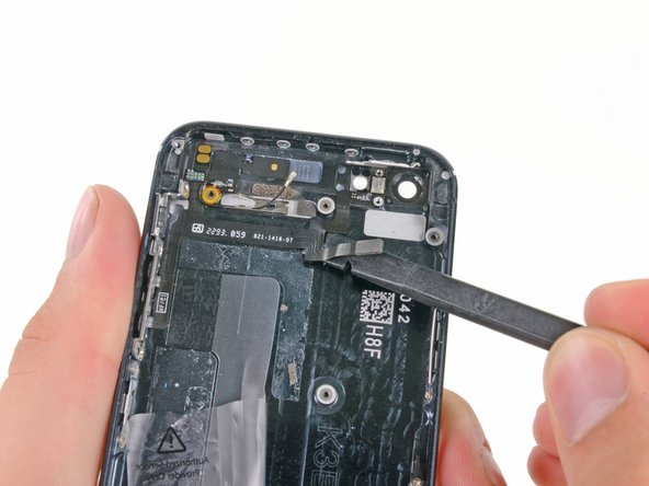 Use the flat edge of a spudger to pry the cable up from the adhesive securing it to the rear case.