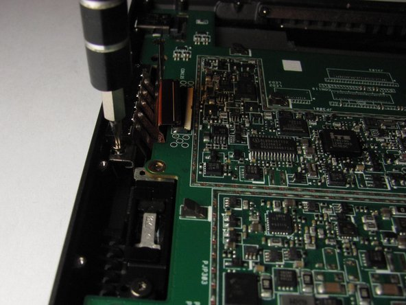 Unscrew the two T5 torx screws located on each side of the charging port.