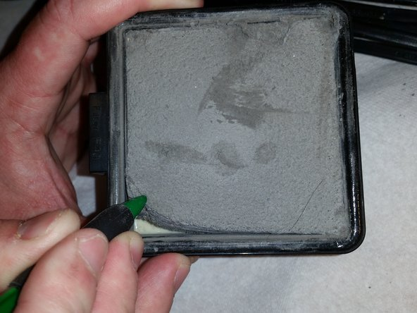 Use a prying tool, such as a spudger, to separate the foam filter from the larger HEPA filter.