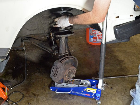 Slowly lower the jack and guide the strut assembly down and out of the car.