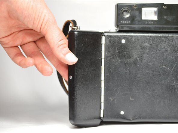 Open the battery compartment on the back left of your Polaroid.