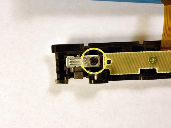 Drehe die Kreuzschlitzschraube heraus und hebele vorsichtig die Metallplatte vom Joy-Con ab (eine Pinzette kann helfen). Halte den Sicherungsriegel dabei fest, so dass die Feder nicht herausspringen kann.
