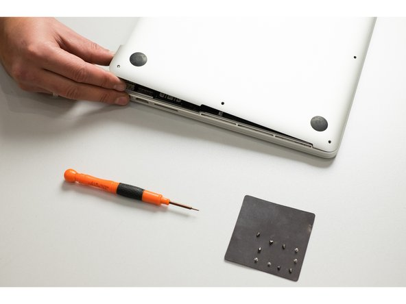 Lifting from the edge nearest the clutch cover, lift the lower case off the MacBook Pro.