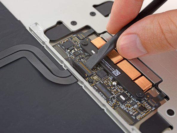 Using a spudger, flip open the retaining flap on the keyboard ribbon cable ZIF connector.