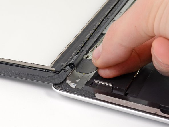 Using your fingers, pull the touchscreen ribbon cable out of its recess in the aluminum frame.