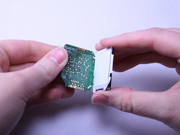 Once the white backing of the screen is exposed, carefully flip the two pieces, the motherboard and the screen, over while they are still connected.
