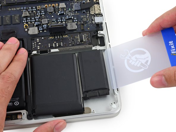 Push a plastic card between the right-most battery cell and the upper case, cutting the adhesive between the two.