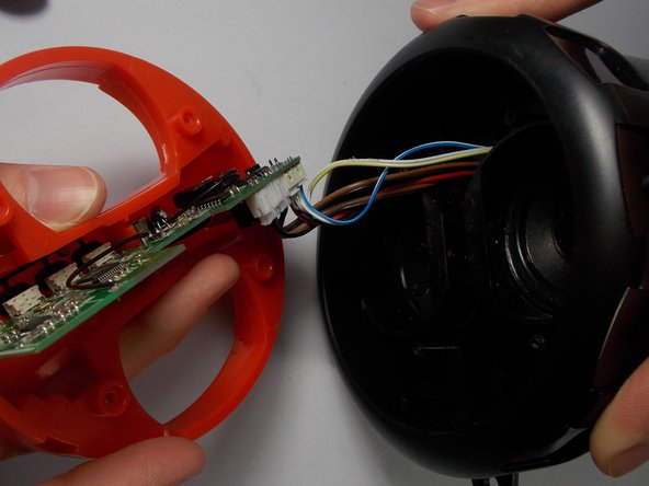 Pull out the red interface plate to expose the wires that were previously hidden between the black faceplate and red interface plate.