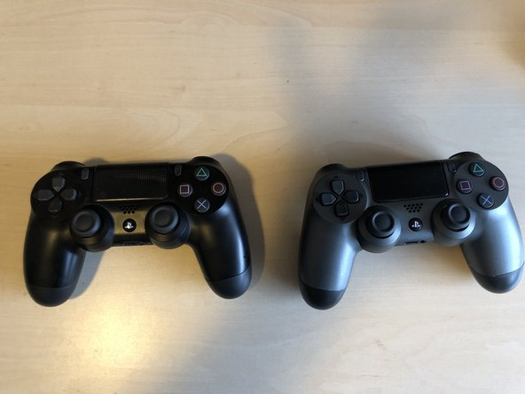 The black controller is an original Sony V2. The silver one is fake. The front housing looks good so far.