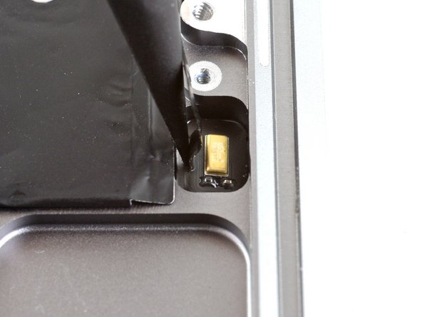 Use the pointed end of a spudger to carefully pry one of the remaining microphones out of its recess in the upper case.