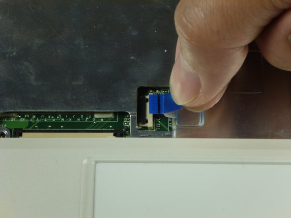 Slide out the touchpad's ribbon connector by pulling the blue tab to the right.