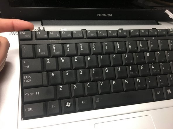 Remove the keyboard slowly. It will be attached to the laptop by a plastic connector, which can be disconnected from the laptop by pulling gently.