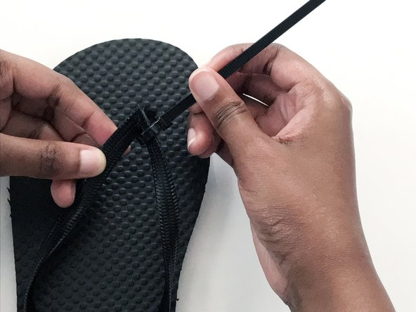 Tighten the loop by pulling on the tail end of the zip tie.