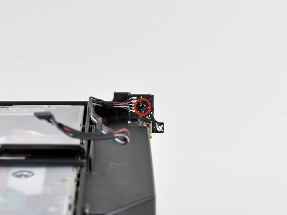 Remove the 5 mm Phillips screw securing the IR board to the optical drive bracket.