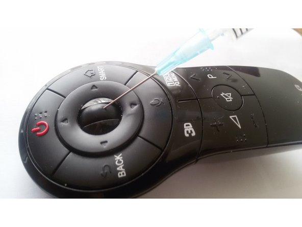 Injectienaald in het rubberen wieletje drukken tot je de as voelt.