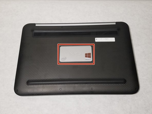 Fermez l'ordinateur portable, retournez-le et retirez le panneau arrière à l'aide d'un tournevis à tête plate. Le panneau sera suspendu par les charnières une fois ouvertes.