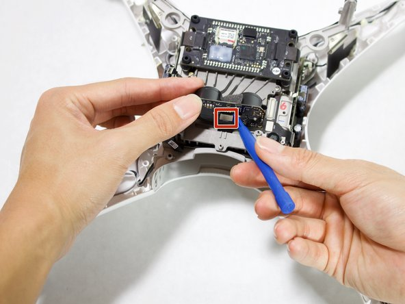 Pry the ribbon cable off the ultrasonic sensor using a plastic opening tool.