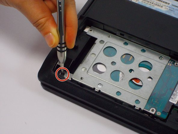 Remove the 9mm Phillips head screw in the left bottom corner of the hard drive with the PH0 bit.