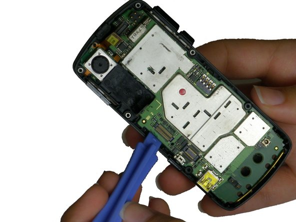 Use a plastic opening tool to gently pry the motherboard up until you can tilt it with your fingers. Unhook it from the casing and slowly pull it out.