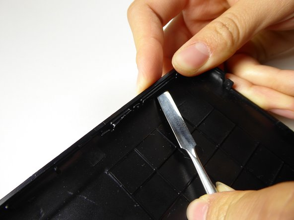 Using a metal spudger and/or your fingers, press the volume button in and lift the outside tab.