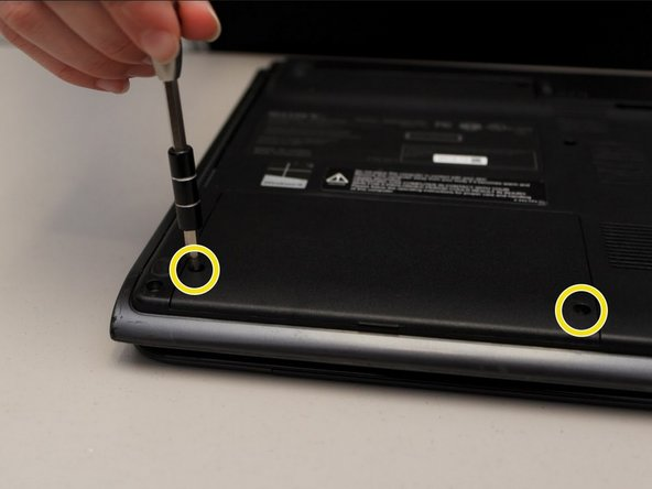 Locate and remove the two Phillips #0 screws on the hard drive cover with the screw driver.