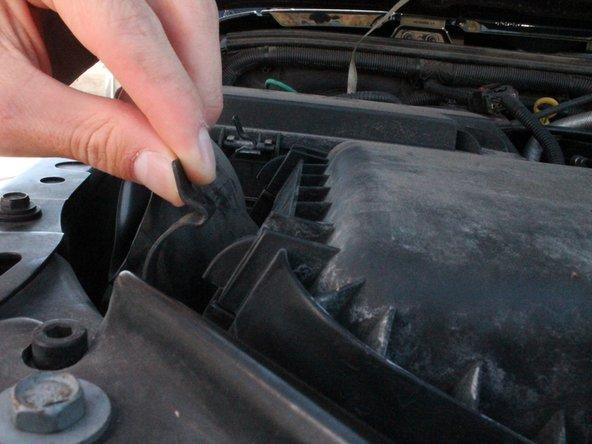 To unlock the air filter box, grasp each clip and pull the clip away from the air filter box.