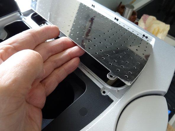 Hebe die Tassenwärmeplatte heraus. Sie lässt sich wie eine Buchseite aufklappen.