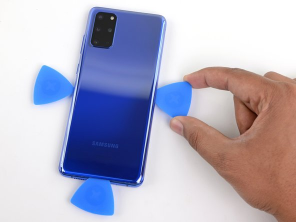 Slide the pick all along the right edge of the phone to separate the back cover's adhesive.