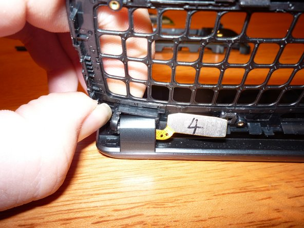 The case comes off the front display by bending the frame around clips in the hinges. On the side with the cable, bend the outer edge toward the screen to get it around a post.