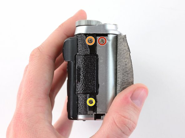 Use tweezers or a fingernail to peel back the rubber cover on the right handgrip.