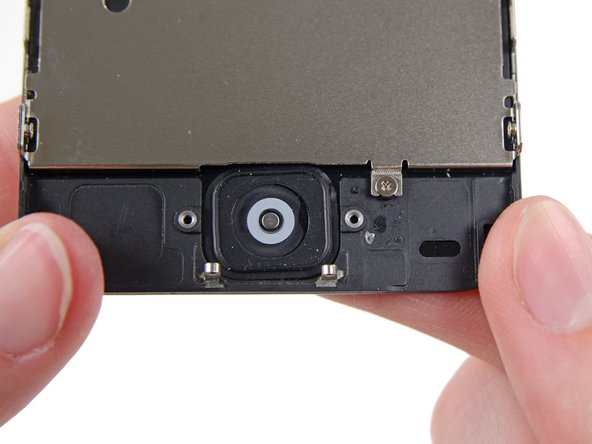 Gently push the top right corner of the home button up away from the front panel.