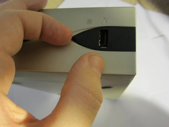Push down and slide the tabs on both sides of the back of the printer away from the device to remove the tabs.