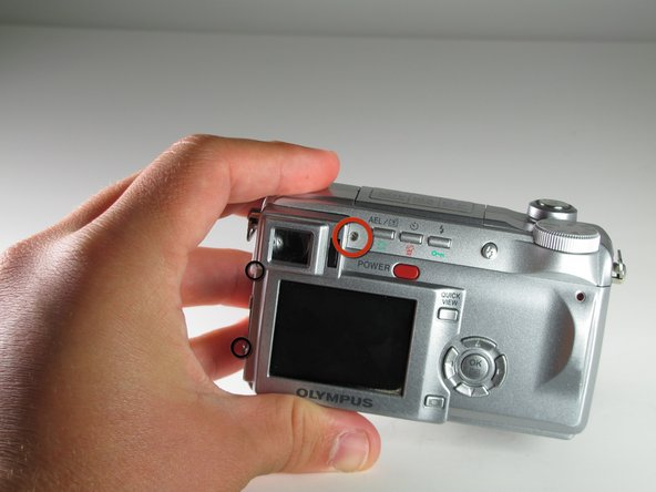 Remove the 4 mm screw directly to the right of the viewfinder on the back side of the camera using a Phillips #00 screwdriver.