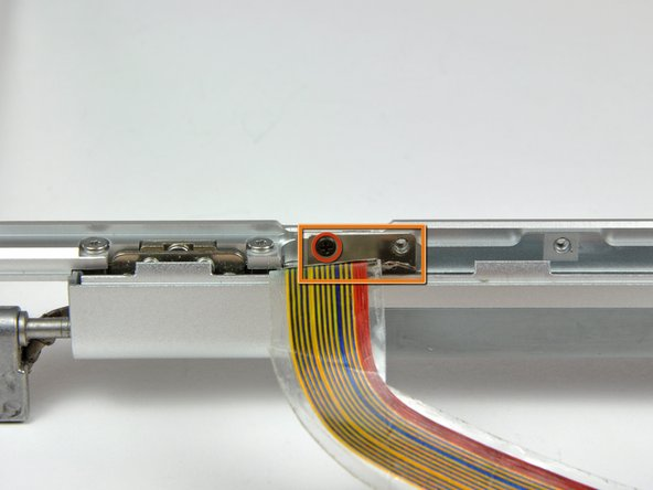Remove the single black Phillips screw from behind the display data cable.