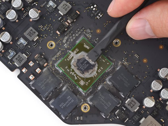 Use a spudger to gently lift the excess thermal paste residue off of the GPU.