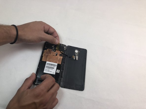 Remove the opaque yellow sticker that indicates where the fingerprint scanner is connected to the back of the device.