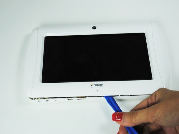 Use a plastic opening tool to detach the clips on the inside of the device.