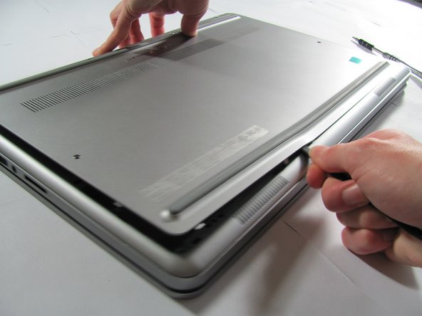 Use a spudger to remove the base cover from the rest of bottom cover.