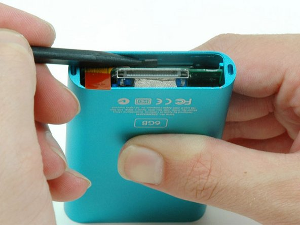 Use a spudger to pull back on the small black plastic tab holding the click wheel in place.