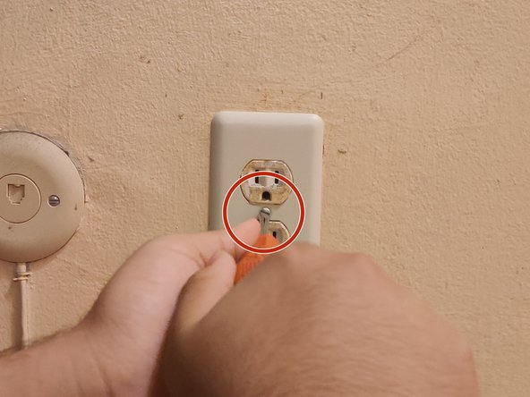 Use the flathead screwdriver to remove the screw from the outlet.