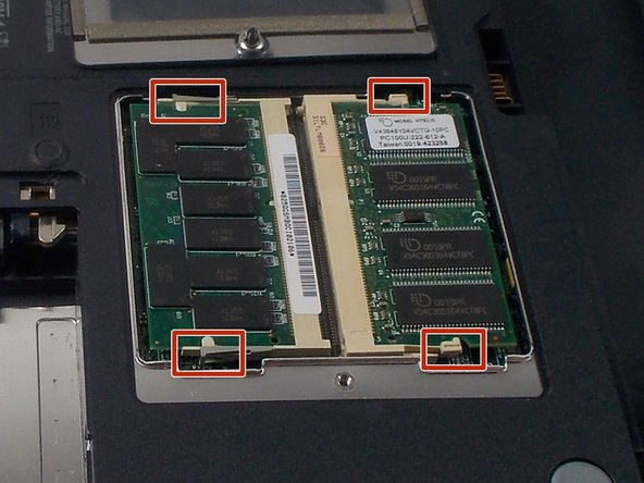 Underneath are the RAM boards. They are secured by two plastic clips each. Locate these to continue removal.