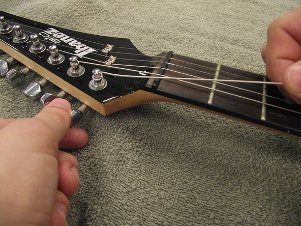 If desired, lay a cloth or towel on the table to avoid scratching the table or the surface of the guitar.