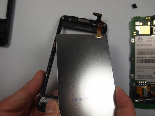 Once the orange tabs are pulled back, use a plastic wedge to detach the LCD screen.