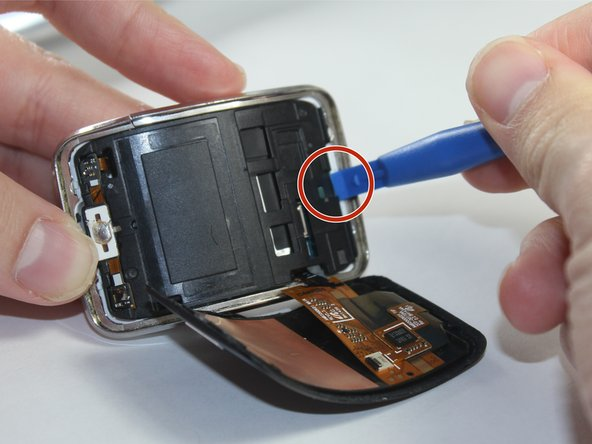 Use a plastic opening tool to  gently pry upwards on the plastic motherboard assembly.
