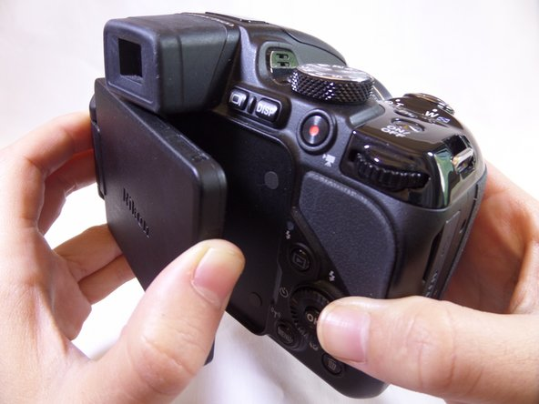Position the back of the camera facing you and open the LCD screen to the left.