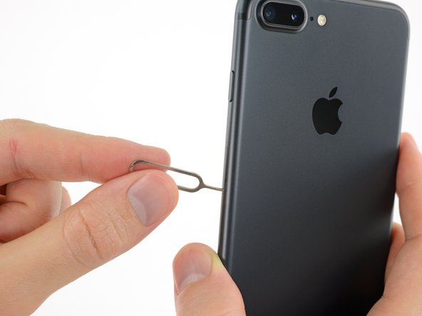 Insert a SIM card eject tool or a paperclip into the small hole in the SIM card tray.