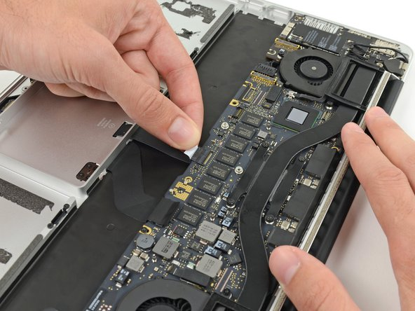 Grasp the plastic pull tab and pull the trackpad ribbon cable out of its socket.